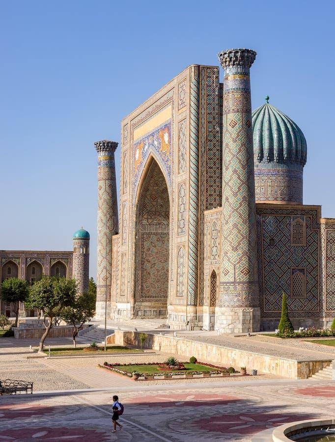 Ensam skolaflicka som promenerar fyrkantiga Registan - Samarkand, Uzbekistan arkivbild
