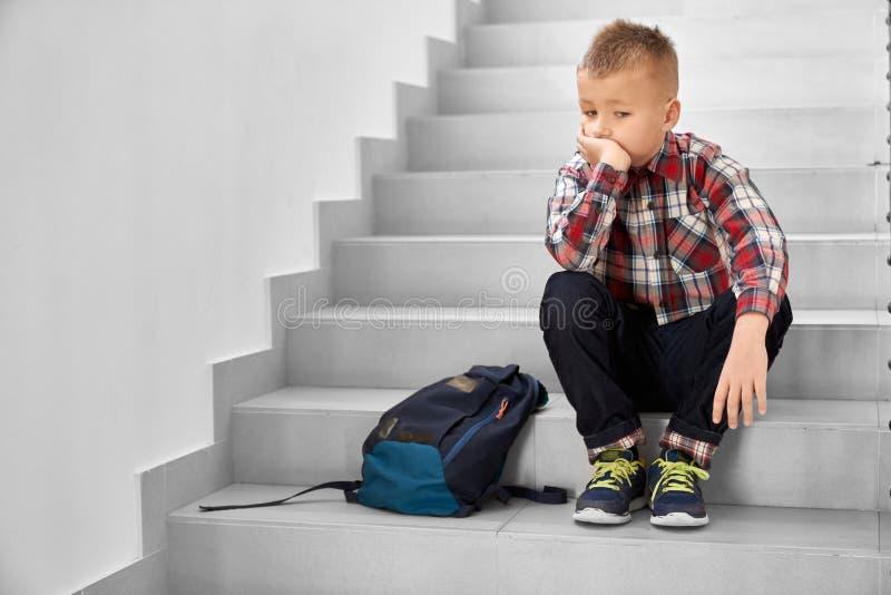 Ensam skolpojke som sitter p? trappuppg?ng i skola som t?nker royaltyfri fotografi