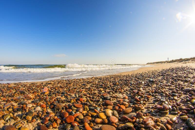Ensam strand av Östersjön med kiselstenar, bränning och blå himmel royaltyfri foto