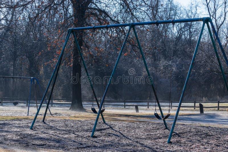 Ensam swingset i vintern royaltyfria bilder