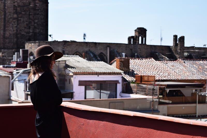 Ensam ung kvinna i brun hatt från baksidan som tänker på terraс e, Barcelona fotografering för bildbyråer
