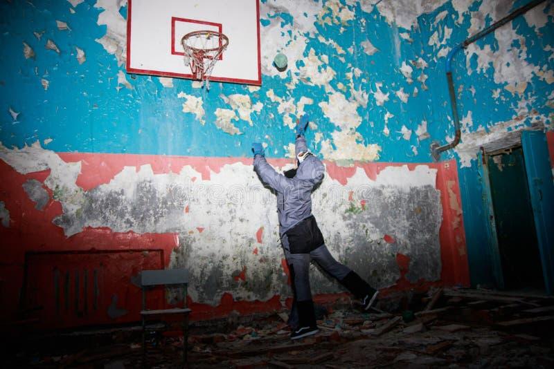 Ensam ungeflicka i övergiven gammal barnskola, äldre väggar med gula blåa gröna väggar för spruckna målarfärger, lämnad kvar kons royaltyfria bilder