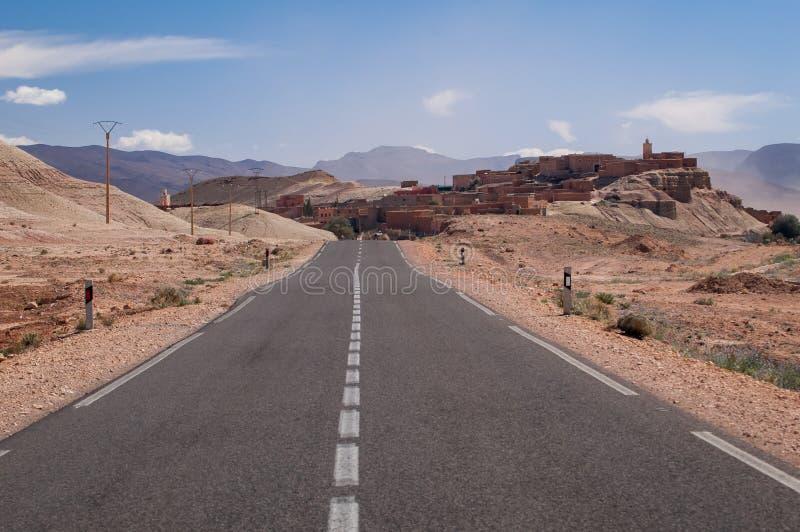 Ensam väg till en liten by i öknen av Marocko royaltyfri fotografi