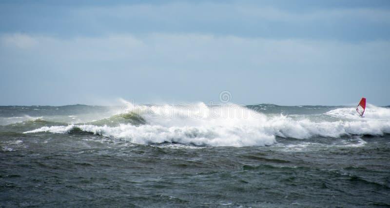 Ensam vindsurfare som rider vågorna arkivbild