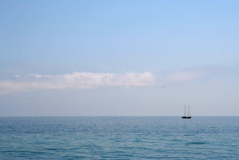 Ensam yacht i det lugna blåa havet royaltyfri fotografi