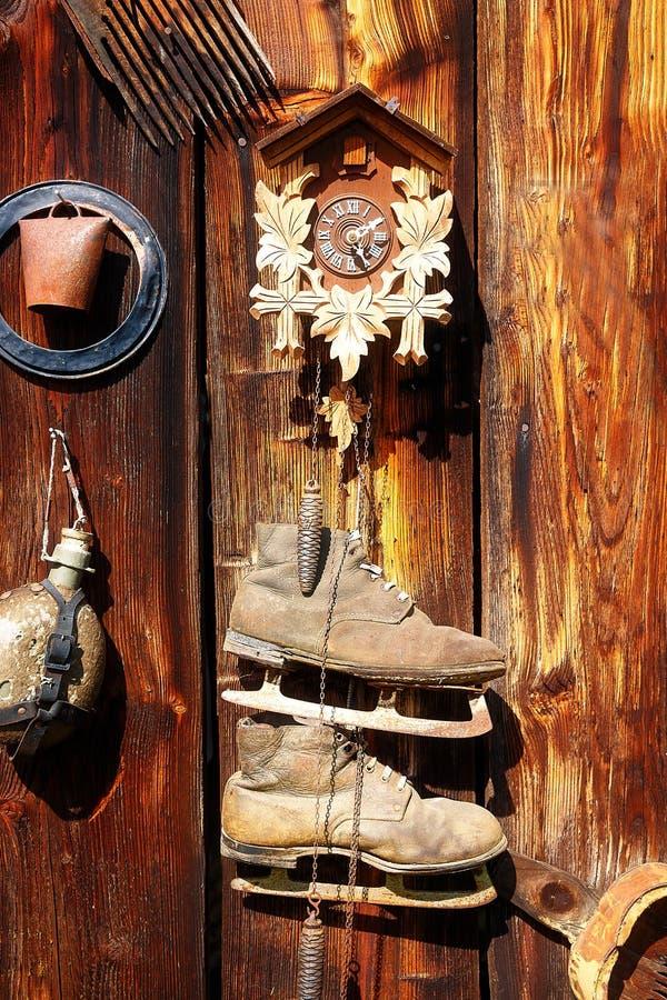 Ensambladura retra antigua del objeto del viejo estilo en una pared de madera montante rústico Reloj, campana, patines viejos y o fotos de archivo libres de regalías