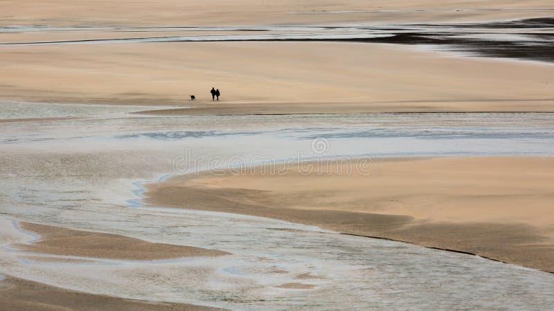Ensamma fotgängare med hunden på Crantock sätter på land, Cornwall arkivbilder