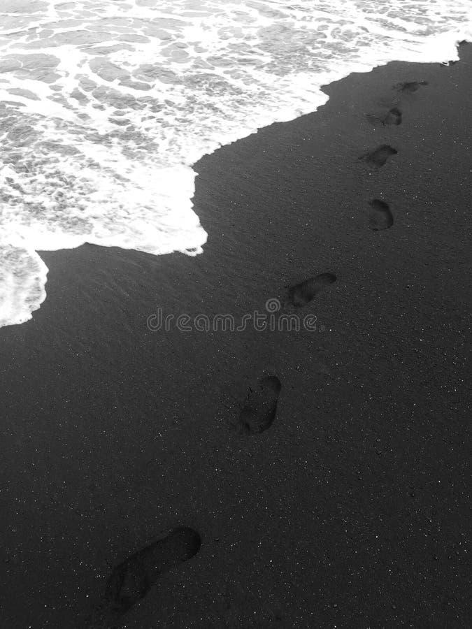 Ensamma fotspår, efter gå på på den svarta sandstranden vid havet - Maui, Hawaii royaltyfri fotografi