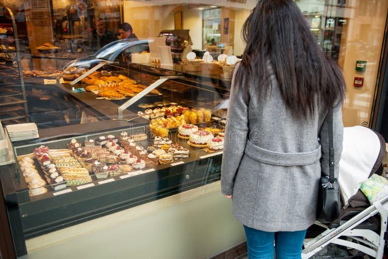 Ensamstående mamma som beundrar fransk söt bakelse i bagerifönster royaltyfria foton