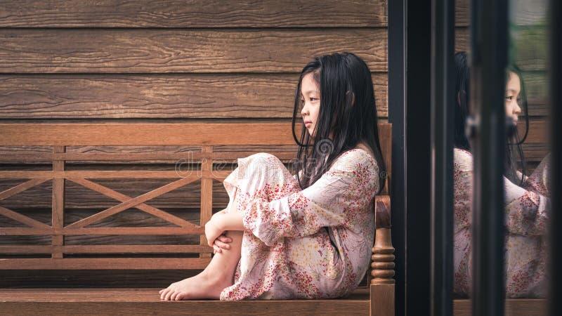 Ensamt asiatiskt barn som sitter bredvid fönster bara fotografering för bildbyråer