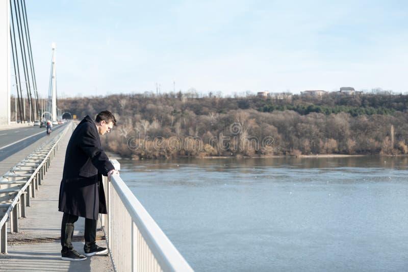 Ensamt deprimerat och angeläget mananseende på bron med självmords- tankar som svikas i folk som ser ner förberett till jumen arkivbilder