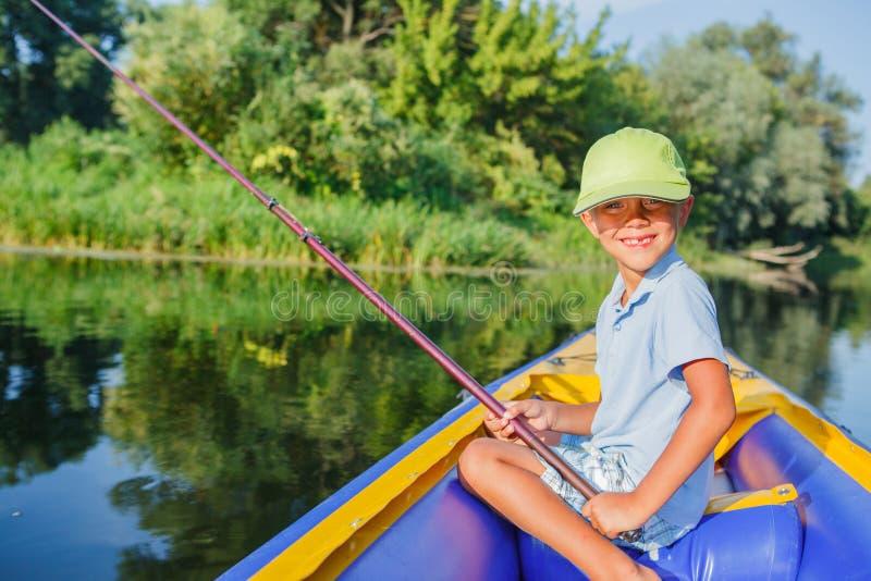 Ensamt fiske för litet barn på floden royaltyfri foto