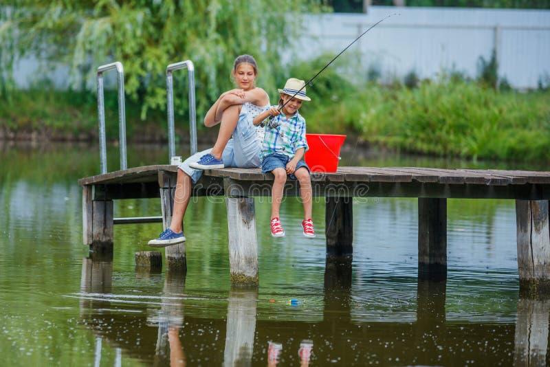 Ensamt fiske för litet barn på floden arkivfoton