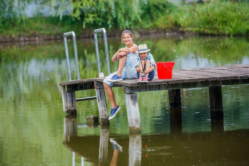 Ensamt fiske för litet barn på floden arkivbild
