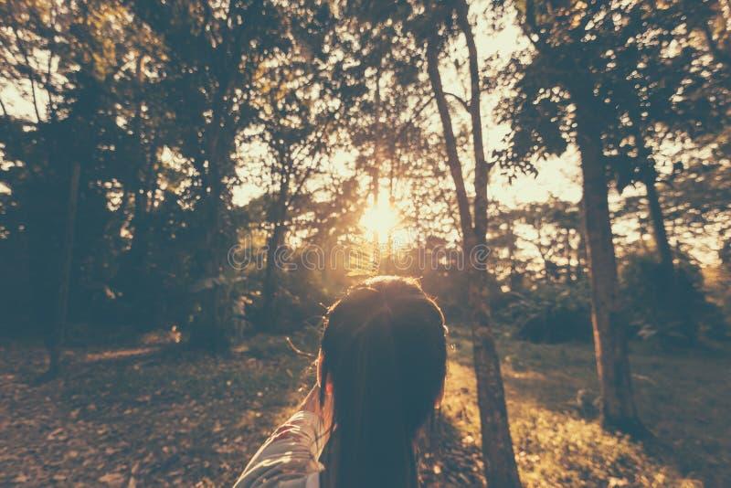 Ensamt flickaanseende i skogen och soluppgång i morgonen arkivfoto