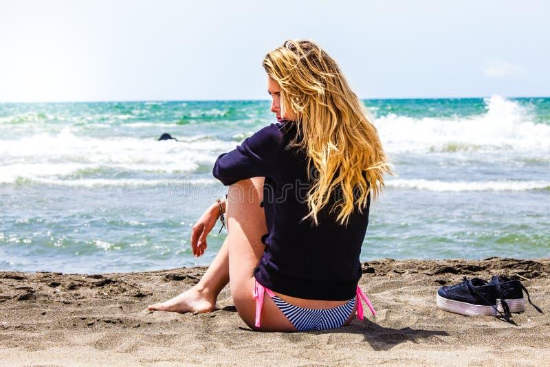 Ensamt flickasammanträde på stranden med havet Fundersamt och älska Förälskad besvikelse arkivfoton
