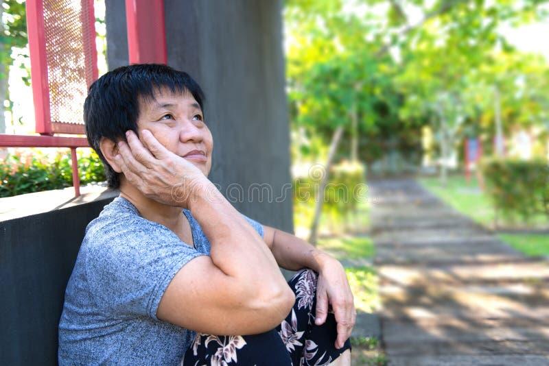Ensamt högt kvinnasammanträde utanför royaltyfri foto