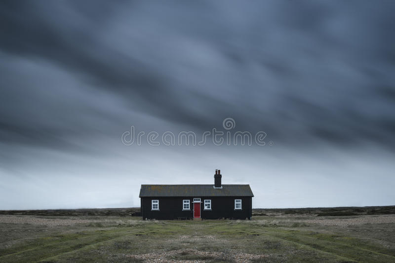 Ensamt isolerat hus för fjärrkontroll under mörk stormig himmel under Wint royaltyfria foton
