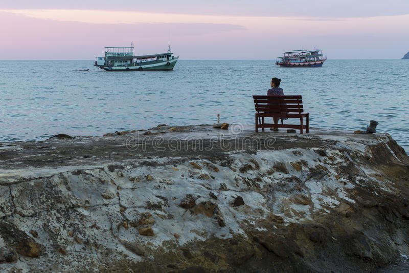 Ensamt kvinnasammanträde på den steniga kusten arkivbilder