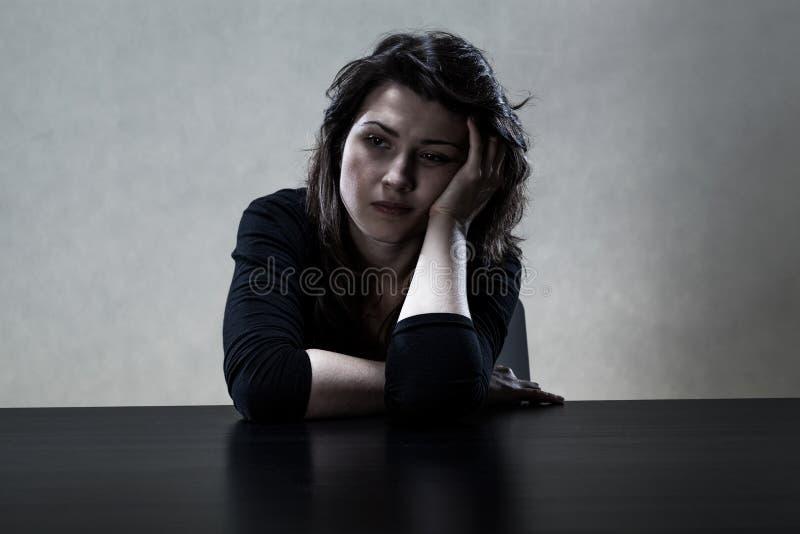 Ensamt ledset flickasammanträde på tabellen royaltyfri foto