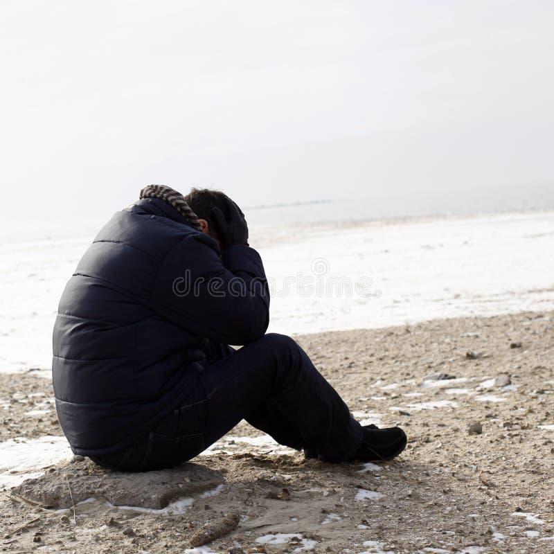 Ensamt mansammanträde på sanden royaltyfri fotografi
