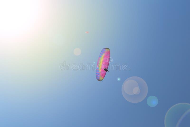 Ensamt paragliderflyg i den bl?a himlen mot bakgrunden av moln Paragliding i himlen p? en solig dag royaltyfri foto