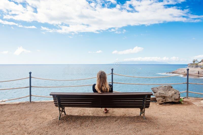 Ensamt sammanträde för ung kvinna på bänken royaltyfri bild
