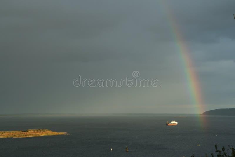 Ensamt skepp p? floden och en regnb?ge i himlen arkivfoto