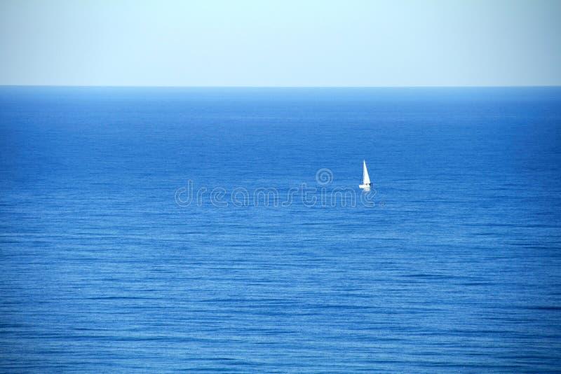 ensamt sväva för segelbåt mot det blåa havet royaltyfria foton