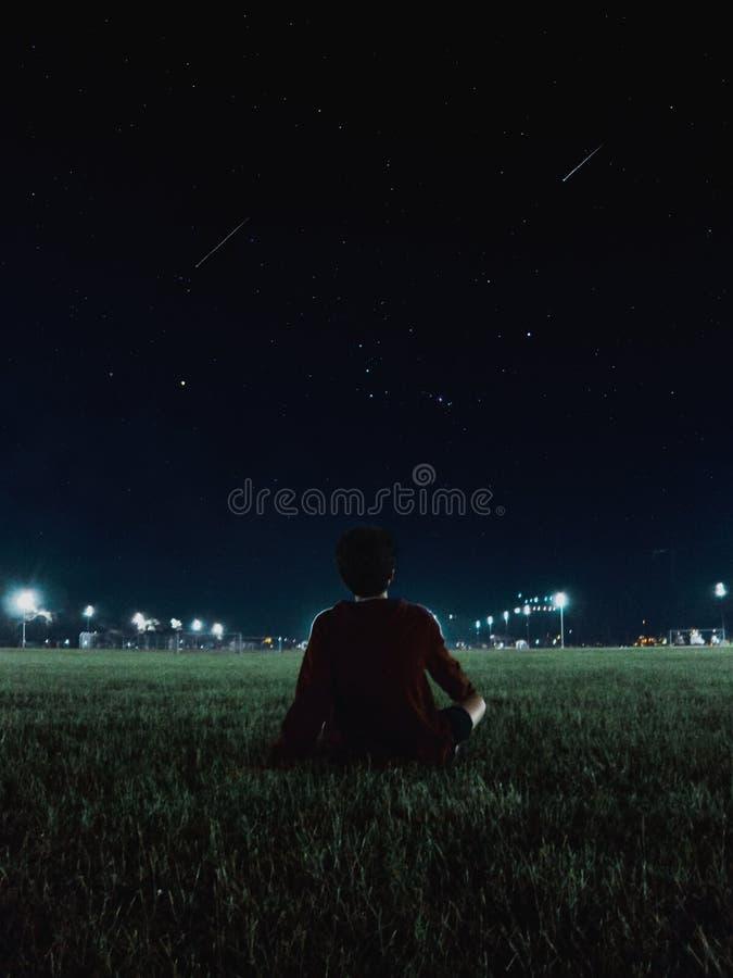 Ensamt tonårigt i ett fält som räknar stjärnor arkivbild