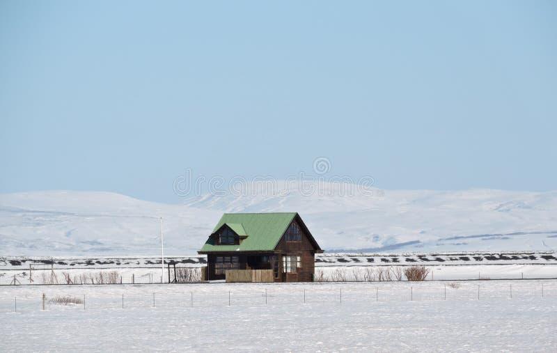 Ensamt traditionellt icelandic hus som omges av snölandskap arkivbilder
