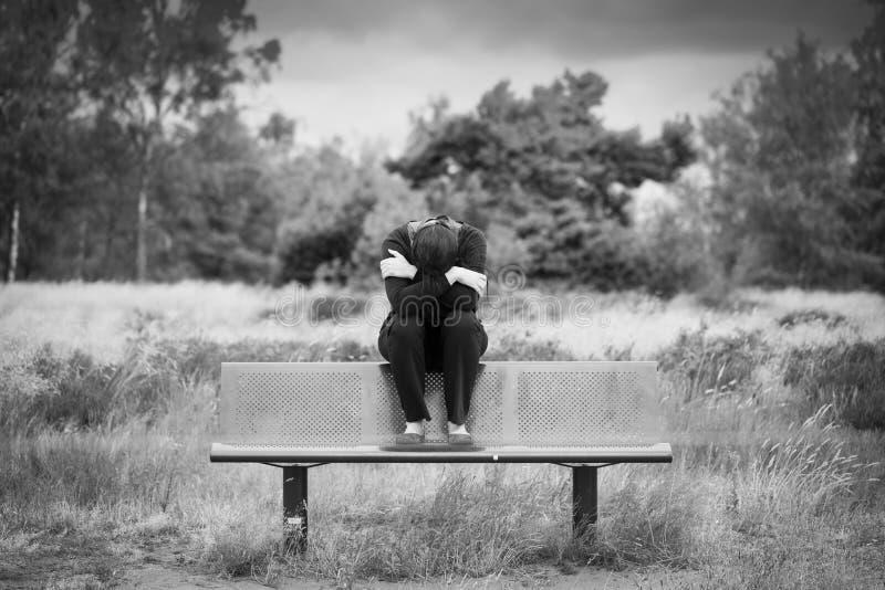 Ensamt ungt deprimerat ledset kvinnasammanträde på en bänk med armar korsade framme av hennes framsida monokrom stående arkivfoto