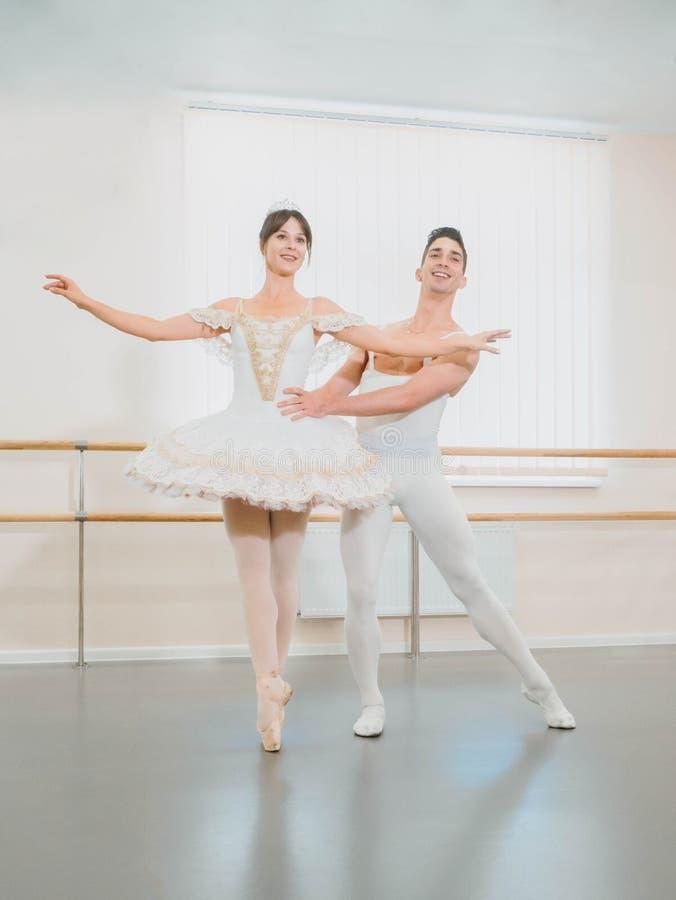 Ensayo en el pasillo o el estudio del ballet con el interior del minimalismo Pares sensuales profesionales jovenes en trajes herm fotos de archivo