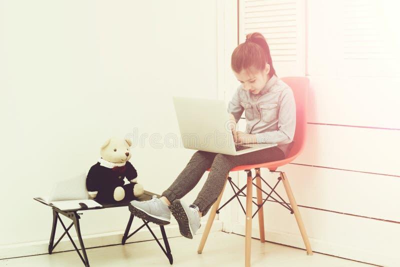Enseñanza de la informática de la muchacha linda que usa el ordenador portátil foto de archivo libre de regalías