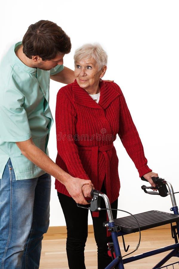 Enseñanza del fisioterapeuta usando el caminante fotografía de archivo