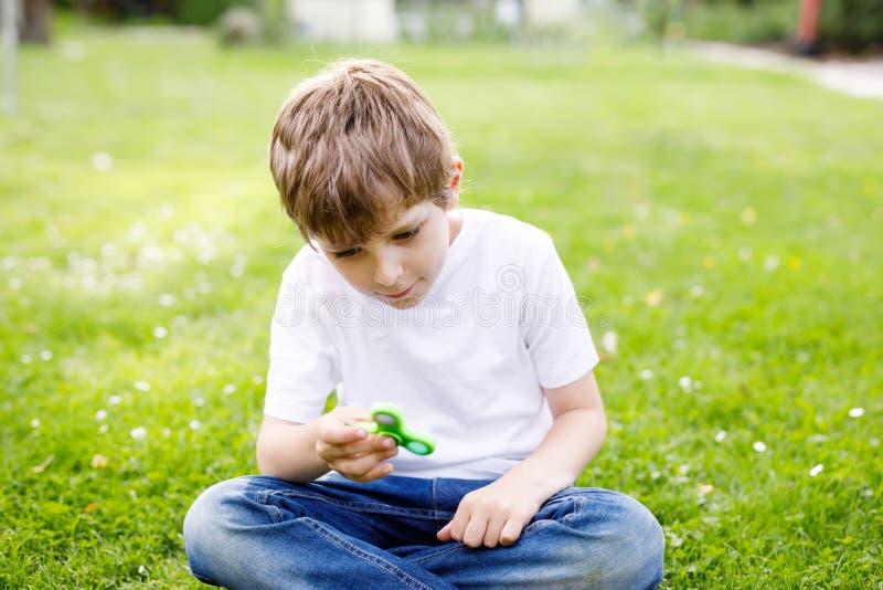 Enseñe al niño que juega con el tri hilandero de la mano de la persona agitada al aire libre imagen de archivo libre de regalías