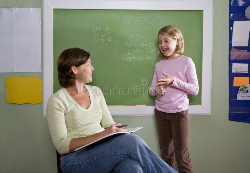Enseñe la muchacha y al profesor por la pizarra en sala de clase imagenes de archivo