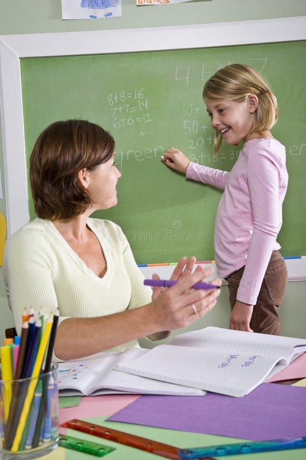 Enseñe la muchacha y al profesor por la pizarra en sala de clase fotografía de archivo