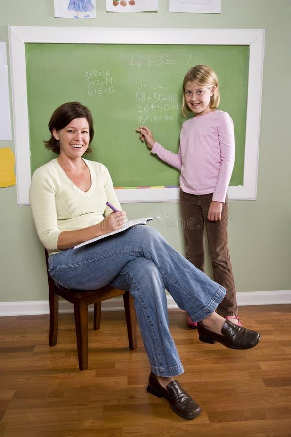 Enseñe la muchacha y al profesor por la pizarra en sala de clase fotografía de archivo libre de regalías
