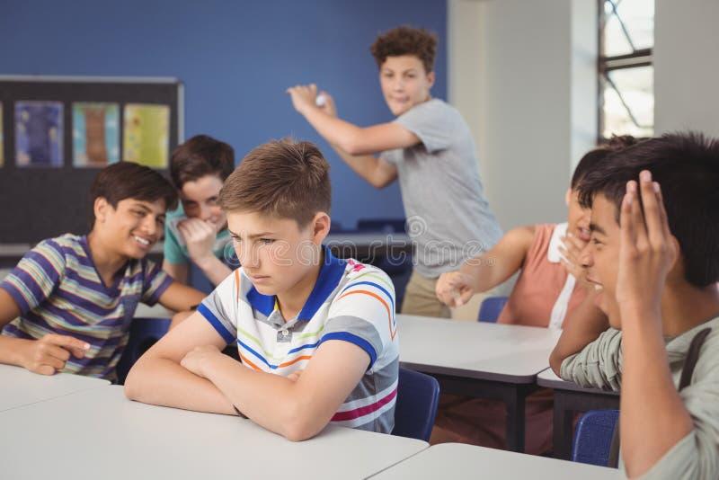 Enseñe a los amigos que tiranizan a un muchacho triste en sala de clase fotografía de archivo libre de regalías
