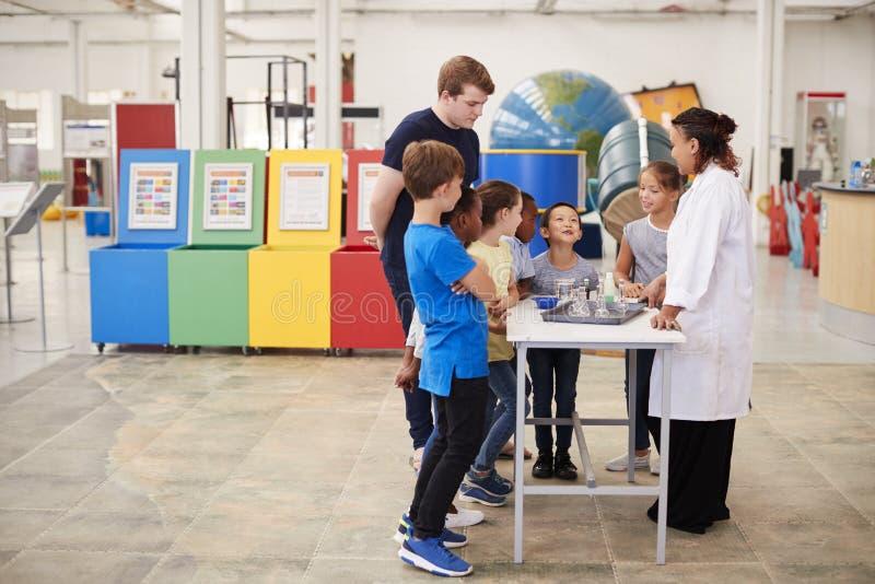 Enseñe a los niños que miran una presentación en un centro de la ciencia fotografía de archivo