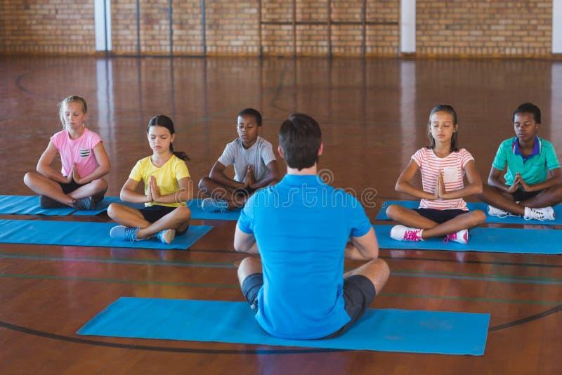 Enseñe los niños y al profesor que meditan durante clase de la yoga imagenes de archivo