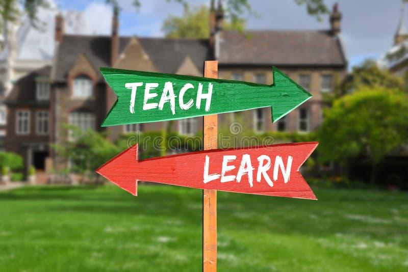 Enseñe y aprenda en diversas direcciones con las flechas de madera coloreadas delante del campus universitario imagen de archivo