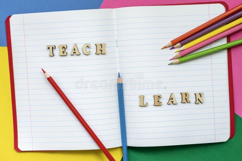 Enseñe y aprenda, las palabras en cuaderno abierto, los creyones coloridos y las hojas de papel coloreadas Concepto de educación, fotos de archivo