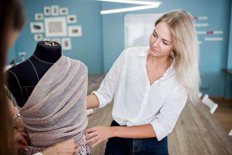 Enseende bärande vit skjorta för nätt kvinna ser skräddarens attrapp Mode skräddares seminarium royaltyfri bild
