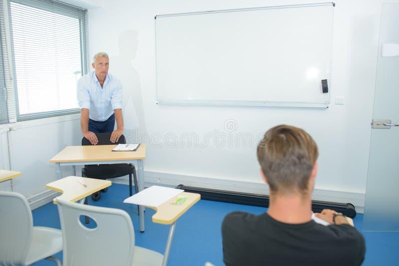 Enseignant aidant un élève après la classe photos libres de droits