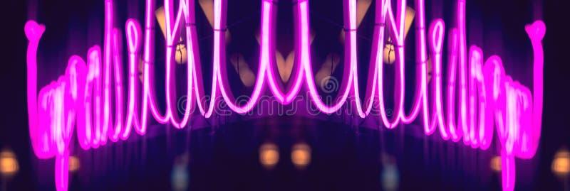 Enseigne au néon rose abstrait avec le fond brouillé de lumière de tube au néon photos stock