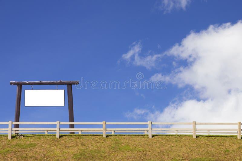 Enseigne et barrière en bois avec l'herbe et le ciel bleu images stock