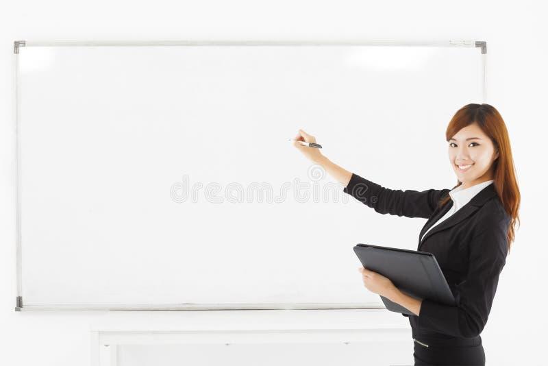 Enseignement de sourire asiatique de femme d'affaires avec un conseil blanc images stock