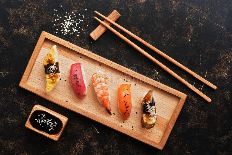 Ensemble assorti de sushi sur un fond rustique foncé Sushi japonais de nourriture d'un plat en bois, sauce de soja, baguettes Vue photos libres de droits